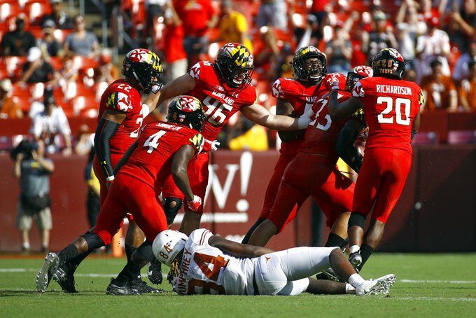 Maryland players celebrate in front of Texas wide receiver Lil'Jordan Humphrey (84) after Maryland linebacker Tre Watson, second from right, intercepted a pass intended for Humphrey in the second half of an NCAA college football game, Saturday, Sept. 1, 2018, in Landover, Md. Maryland won 34-29. (AP Photo/Patrick Semansky)