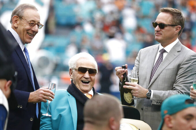 Miami Dolphins owner Stephen Ross, left, toasts, former head coach Don Shula, during a half time celebrating the 1972 undefeated team during at an NFL football game against the Cincinnati Bengals, Sunday, Dec. 22, 2019, in Miami Gardens, Fla.To the right is CEO Tom Garfinkel. (AP Photo/Brynn Anderson)