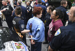 A pair of Hopkins students are arrested after blocking a police van carrying fellow protestors, Wednesday, May 8, 2019. Baltimore police arrested seven people as they ended a monthlong sit-in in the lobby of an administrative building at Johns Hopkins University, where protesters have demonstrated against the creation of a campus police force and the institution's contracts with the U.S. Immigrations and Customs Enforcement agency. (Jerry Jackson/The Baltimore Sun via AP)