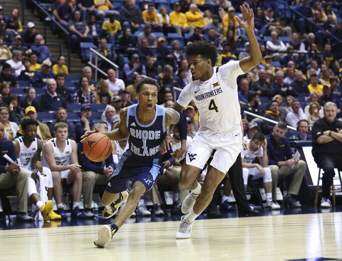 Rhode Island guard Fatts Russell (1) drives the ball up court as he is defended by West Virginia guard Miles McBride (4) during the first half of an NCAA college basketball game Sunday, Dec. 1, 2019, in Morgantown, W.Va. (AP Photo/Kathleen Batten)
