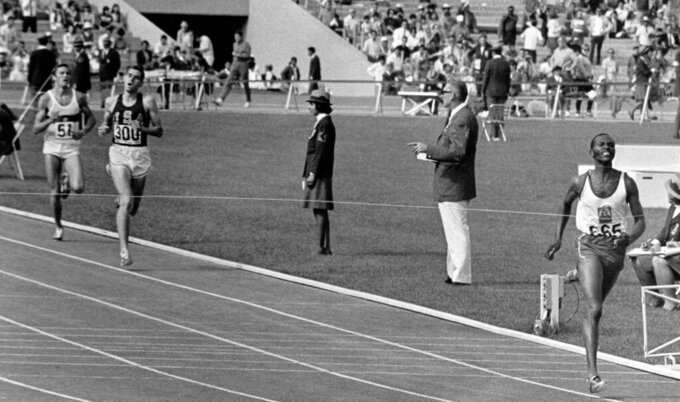 FILE - In this Oct. 20, 1968 file photo, Kipchoge Keino of Kenya hits finish line of 1968 Olympics 1500 meter run Oct. 20, 1968 in 3 minutes, 34.9 seconds for new Olympic record in Mexico City, Mexico. Kenyan athlete Jipcho has died at the age off 77, it was reported on Friday, July 24, 2020.  Jipcho was famous for being the runner who sacrificed his own hopes of a medal to help teammate Kip Keino beat American and heavy favorite Jim Ryun to the gold medal in the 1,500 meters at the 1968 Mexico City Olympics. (AP Photo, File)