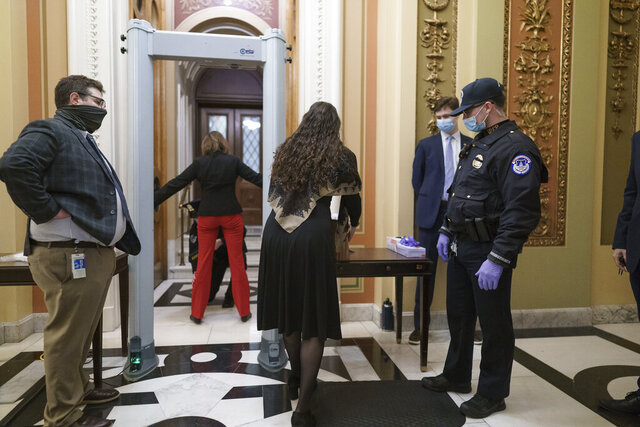 Congressional staff passes through a metal detector and security screening as they enter the House chamber, new measures put into place after a mob loyal to President Donald Trump stormed the Capitol, in Washington, Tuesday, Jan. 12, 2021. Democrats are set to pass a resolution calling on Vice President Mike Pence to invoke constitutional authority under the 25th Amendment to oust Trump. (AP Photo/J. Scott Applewhite)