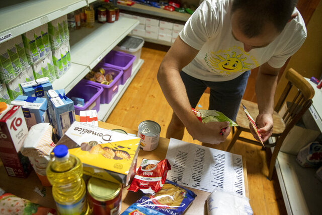 Igor Loparic prepares packages of aid for people in need for help in Pula, Croatia, Tuesday, May 26, 2020. The