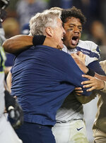 Seattle Seahawks head coach Pete Carroll, left, celebrates with quarterback Russell Wilson after the Seahawks defeated the San Francisco 49ers 27-24 in overtime of an NFL football game in Santa Clara, Calif., Monday, Nov. 11, 2019. (AP Photo/Tony Avelar)
