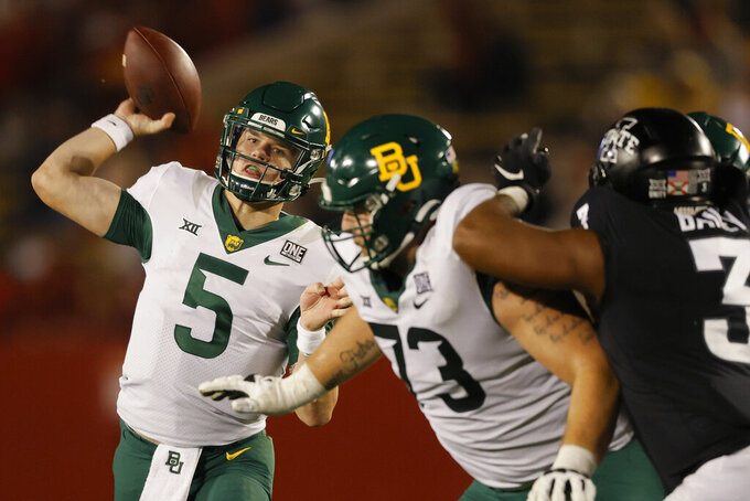 FILE - In this Nov. 7, 2020, file photo, Baylor quarterback Charlie Brewer throws a pass as offensive lineman Jake Burton, center, holds back Iowa State defensive end JaQuan Bailey during the second half of an NCAA college football game in Ames, Iowa. Brewer is set for his 25th consecutive start as Baylor's quarterback, and 37th overall, when Baylor plays Kansas State this week. (AP Photo/Matthew Putney, File)