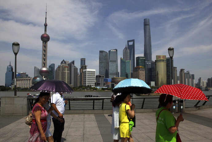 FILE - In this file photo taken Friday, May 22, 2015, people walk on the Bund against buildings in Pudong, China's financial and commercial hub, in Shanghai. China has criticized Washington's efforts to enforce U.S. law abroad following a news report three Chinese banks might be penalized over dealings with North Korea. (AP Photo/Paul Traynor, Filer)