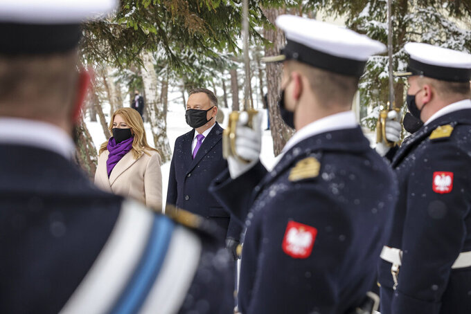 Poland's military stand at attention as President Andrzej Duda welcomes Slovakia's President Zuzana Caputova for a two-day summit with the presidents of Hungary and The Czech Republic marking 30 years of the Visegrad Group, an informal body of political and economic cooperation in the region, at the presidential residence in the Hel Peninsula, Poland, on Tuesday, Feb. 9, 2021.(Jakub Szymczuk / KPRP via AP )