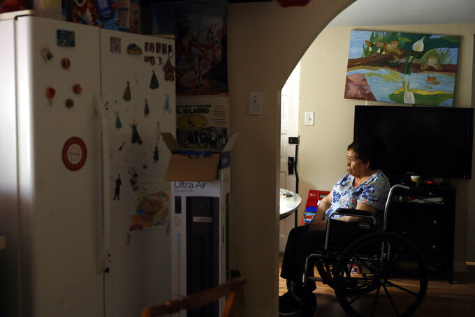 Francisca Perez, 84, sits by the dining table on a wheelchair in her house in Chicago's Little Village neighborhood, Wednesday, June 30, 2021. She suffers from a heart condition, rheumatoid arthritis and depression, among other ailments. Her daughter, Eugenia Rodriguez, hasn't been eligible for insurance coverage after overstaying a visitor visa from Mexico. She used to wake up every two or three hours at night to check on her mother. Since getting health insurance through the Illinois program, her mother has all the medications she needs. (AP Photo/Shafkat Anowar)
