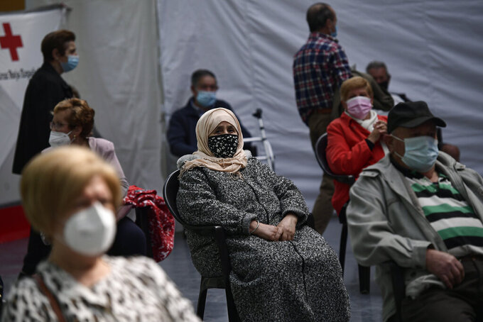Taia Ilhachamia, center, waits 15 minutes after receiving the Pfizer vaccine during a COVID-19 vaccination campaign in Alfaro, northern Spain, Thursday, May 13, 2021. (AP Photo/Alvaro Barrientos)