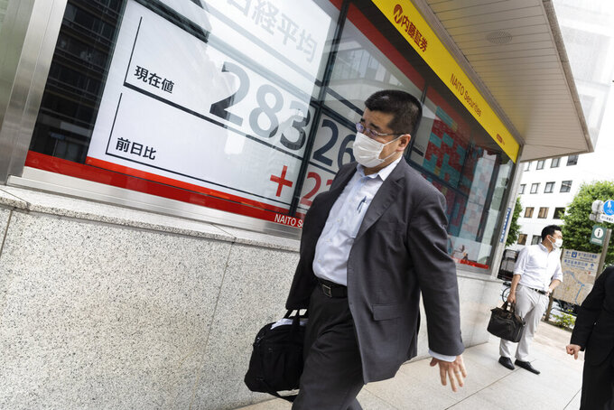 A man walks past monitors showing Japan's Nikkei 225 index at a securities firm in Tokyo Friday, May 21, 2021. Asian shares were mixed Friday after a rebound on Wall Street broke a three-day losing streak. (AP Photo/Hiro Komae)