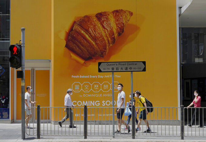 People wearing face masks to prevent the spread of the coronavirus walk past an advertising poster in Hong Kong, Wednesday, May 5, 2021. (AP Photo/Vincent Yu)