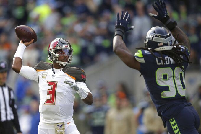 Tampa Bay Buccaneers quarterback Jameis Winston passes under pressure form Seattle Seahawks defensive end Jadeveon Clowney, right, during the first half of an NFL football game, Sunday, Nov. 3, 2019, in Seattle. (AP Photo/Scott Eklund)