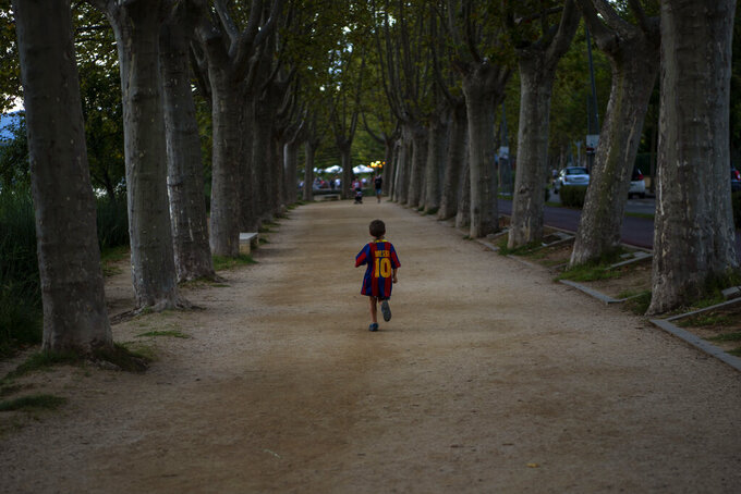 A boy wearing a shirt with the name of Barcelona soccer player Lionel Messi runs on a park in Banyoles, in Girona province, Spain on Wednesday, Sept. 2, 2020. Lionel Messi's future at Barcelona looked no closer to being resolved after the first meeting between the player's father and club officials on Wednesday ended without an agreement, a person with knowledge of the situation told The Associated Press. (AP Photo/Emilio Morenatti)