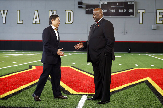 University of Maryland president Wallace Loh, left, shakes hands with new Maryland head football coach Mike Locksley after an NCAA college football news conference, Thursday, Dec. 6, 2018, in College Park, Md. Locksley, Alabama's offensive coordinator, will take over at Maryland after the most tumultuous year in the program's recent history. (AP Photo/Patrick Semansky)