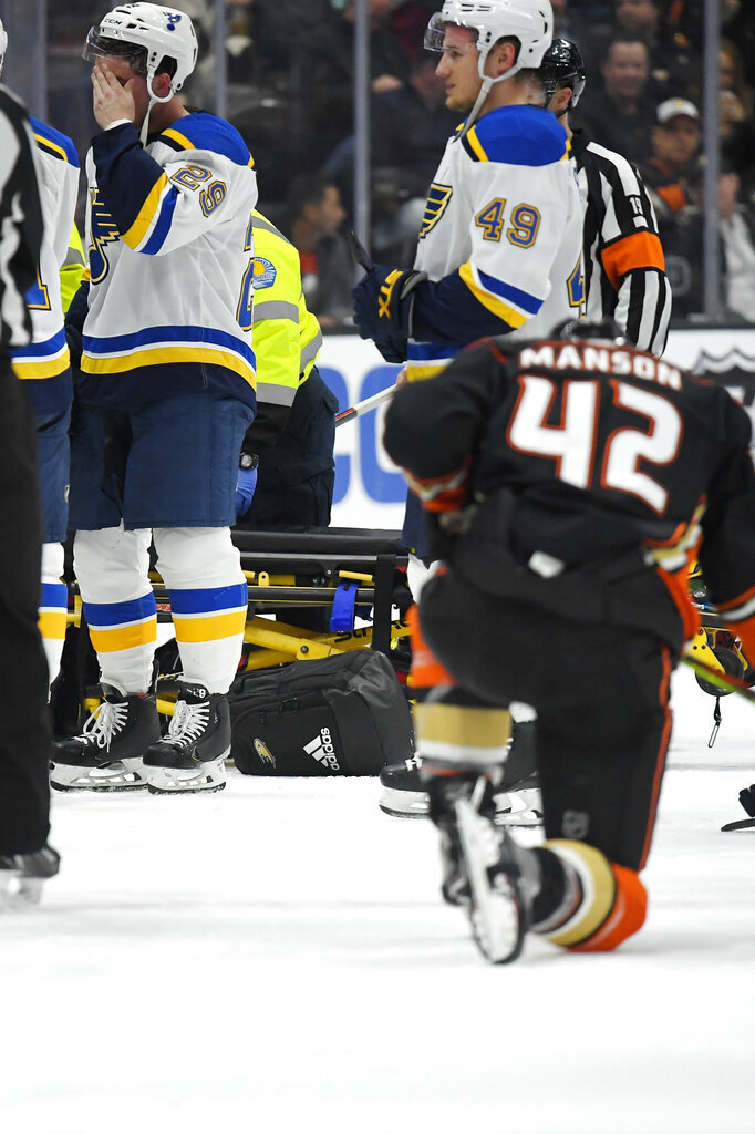 St. Louis Blues defenseman Vince Dunn, left, wipes his faces as Anaheim Ducks defenseman Josh Manson kneels on the ice while Blues defenseman Jay Bouwmeester, who suffered a medical emergency, is worked on by medical personnel during the first period of an NHL hockey game Tuesday, Feb. 11, 2020, in Anaheim, Calif. (AP Photo/Mark J. Terrill)