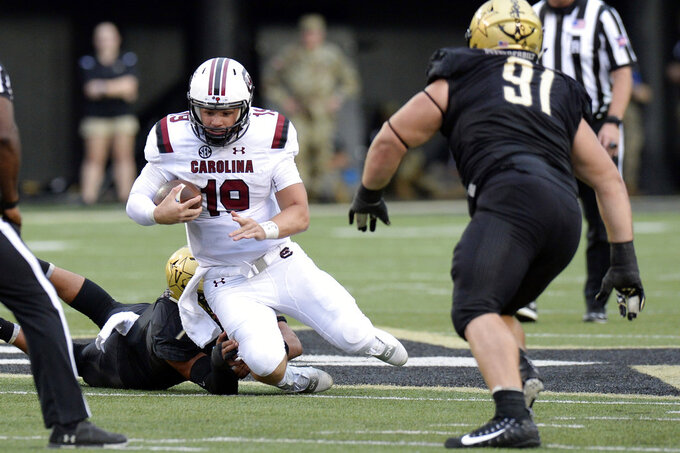 FILE - In this Sept. 22, 2018, file photo, South Carolina quarterback Jake Bentley (19) is forced to the ground by Vanderbilt linebacker Dimitri Moore (7), left, during the second half of an NCAA college football game, in Nashville, Tenn. South Carolina hoped to have more to look forward to on its off week than correcting problems coaches believed were already fixed when the season began.  The Gamecocks (3-3, 2-3 Southeastern Conference) expected improved quarterback play, sure-handed receivers and a stronger run game than the first two years under coach Will Muschamp. (AP Photo/Mark Zaleski, File)
