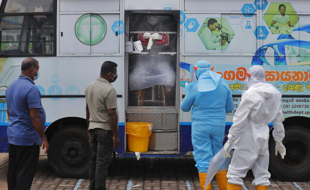 Sri Lankans wait to give swab samples to test for COVID-19 in Minuwangoda, Sri Lanka, Tuesday, Oct. 6, 2020. (AP Photo/Eranga Jayawardena)