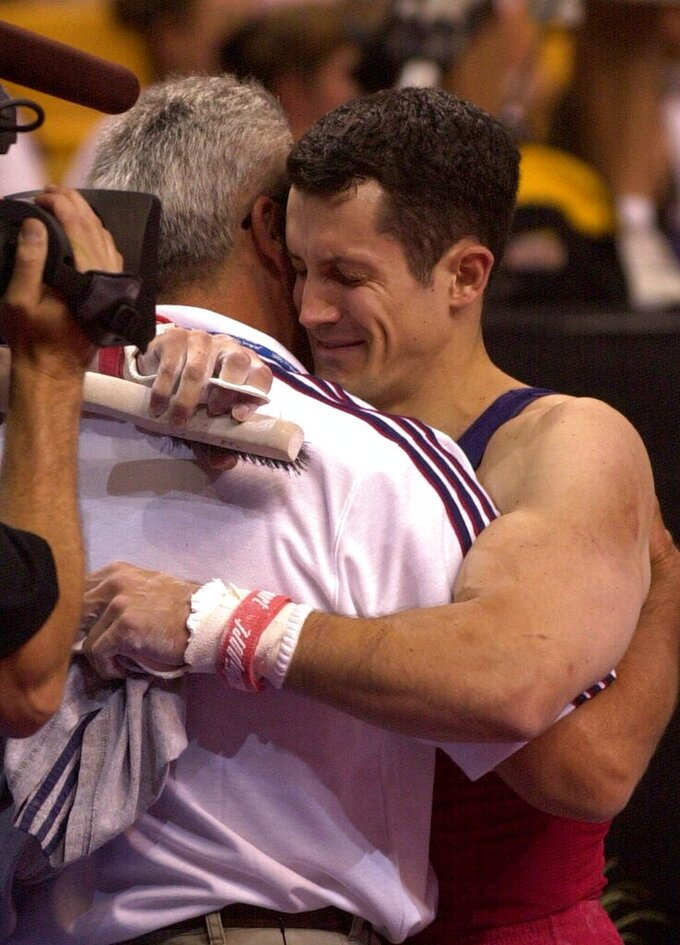 FILE - John Roethlisberger, of Falcon Heights, Minn., hugs his dad Fred after his final event in the men's 2000 U.S. Olympic Gymnastics Trials in Boston, in this Saturday, Aug. 19, 2000, file photo. Roethlisberger was chosen for the U.S. Olympic team. The cutback in NCAA athletic programs due to the COVID-19 pandemic is being felt acutely in men's gymnastics. For decades Division I programs have produced an overwhelming majority of the US Olympic team. The number of Division I programs, however, is shrinking. The University of Minnesota and the University of Iowa will stop offering it as a scholarship sport at the end of the month. That will drop the number of Division I schools to 11. (AP Photo/Elise Amendola, File)