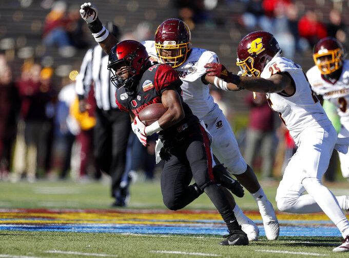 San Diego State wide receiver BJ Busbee, left, tries to break away from Central Michigan linebacker Michael Oliver (7) and defensive back Dishon McNary (25) during the first half of the New Mexico Bowl NCAA college football game on Saturday, Dec. 21, 2019 in Albuquerque, N.M. (AP Photo/Andres Leighton)