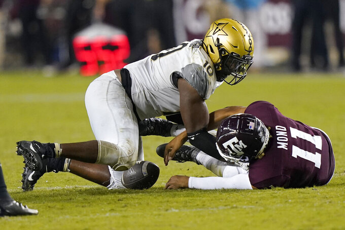 Texas A&M quarterback Kellen Mond (11) fumbles the ball on fourth down as he is hit by Vanderbilt's Dayo Odeyingbo (10) during the second half of an NCAA college football game Saturday, Sept. 26, 2020, in College Station, Texas. Texas A&M won 17-12. (AP Photo/David J. Phillip)