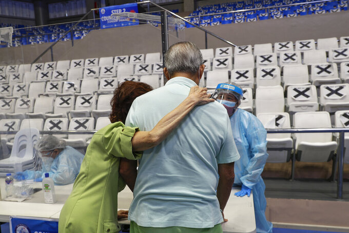An elderly couple talks to a health worker at a vaccination center inside the Makati Coliseum in Manila, Philippines on Tuesday, May 4, 2021. The Philippines started a simultaneous vaccination of the initial 15,000 doses of Russia's Sputnik V COVID-19 vaccines that arrived in the country earlier this week. (AP Photo/Aaron Favila)