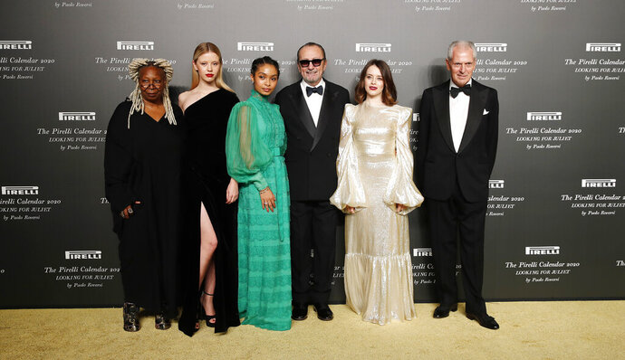 From left, American actress Whoopi Goldberg, British model Mia Goth, American model Yara Shahidi, Italian photographer Paolo Roversi, British actress Claire Foy and Pirelli CEO Marco Tronchetti Provera pose for photographers at the 2020 Pirelli Calendar event in Verona, Italy, Tuesday, Dec. 3, 2019. (AP Photo/Antonio Calanni)