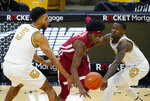 Washington State guard Noah Williams, center, loses control of the ball as he drives between Colorado guards D'Shawn Schwartz, left, and McKinley Wright IV during the second half of an NCAA college basketball game Wednesday, Jan. 27, 2021, in Boulder, Colo. (AP Photo/David Zalubowski)
