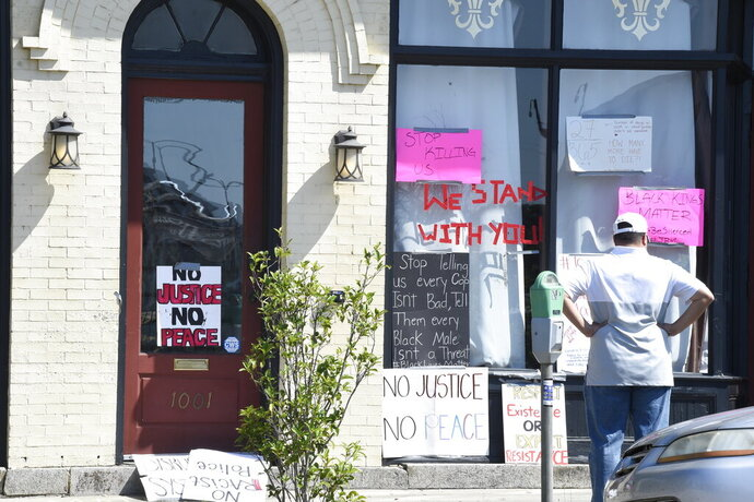 Signs adorn the windows of a restaurant in Columbia, S.C., on Sunday, May 31, 2020, a day after a peaceful protest in response to the death in Minneapolis of George Floyd devolved into violence in downtown Columbia. (AP Photo/Meg Kinnard)