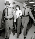FILE - In this Nov. 21, 1981 file photo, Weather Underground member Katherine Boudin is led from Rockland County Courthouse in New City, New York, by sheriff's officers. Chesa Boudin, the son of anti-war radicals Kathy Boudin and his father, David Gilbert, sent to prison for murder when he was a baby, has won San Francisco's tightly contested race for district attorney after campaigning to reform the criminal justice system. The former deputy public defender declared victory Saturday night, Nov. 9, 2019 after four days of ballot counting determined he was ahead of interim District Attorney Suzy Loftus. (AP Photo/Handschuh, File)