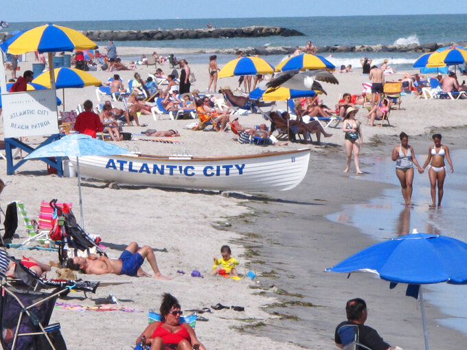 In this June 23, 2014 file photo, beachgoers fill the sand at Atlantic City N.J. On Wednesday, May 12, 2021, New Jersey legislators were scheduled to discuss two proposed measures that could have a far-ranging impact on Atlantic City's future: A bill changing the amount the city's casinos must pay in lieu of property taxes, and a bill extending the state's takeover of Atlantic City's main decision-making power for another four years. (AP Photo/Wayne Parry)