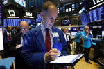 Trader Mark Puetzer, center, works on the floor of the New York Stock Exchange, Tuesday, Oct. 8, 2019. Stocks are opening lower on Wall Street as tensions rose between Washington and Beijing just ahead of the latest round of trade talks. (AP Photo/Richard Drew)