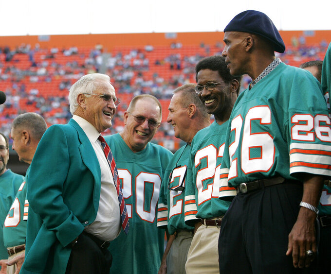 FILE - In this Dec. 16, 2007 file photo former Miami Dolphins coach Don Shula, left, talks with former players from the 1972 undefeated team during a halftime ceremony at a football game against the Baltimore Ravens at Dolphin Stadium in Miami. From left: Shula, Larry Seiple (20), Jim Kiick (21), Mercury Morris (22) and Lloyd Mumphord (26). The perfection of the 1972 Miami Dolphins has earned them the nod as the NFL's greatest team. The 1972 Dolphins edged the 1985 Chicago Bears for the NFL's greatest team in balloting by 59 national media members as part of the NFL's celebration of its 100th season. (AP Photo/Lynne Sladky, file)