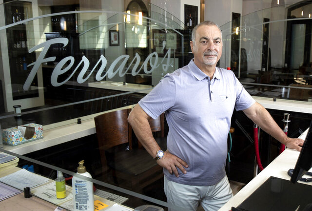 Gino Ferraro poses for a picture at Ferraro's Italian Restaurant & Wine Bar Tuesday, Aug. 11, 2020. Ferraro is one of many local restaurant and small business owners suffering business loss due to the coronavirus pandemic. (Steve Marcus / Las Vegas Sun via AP)