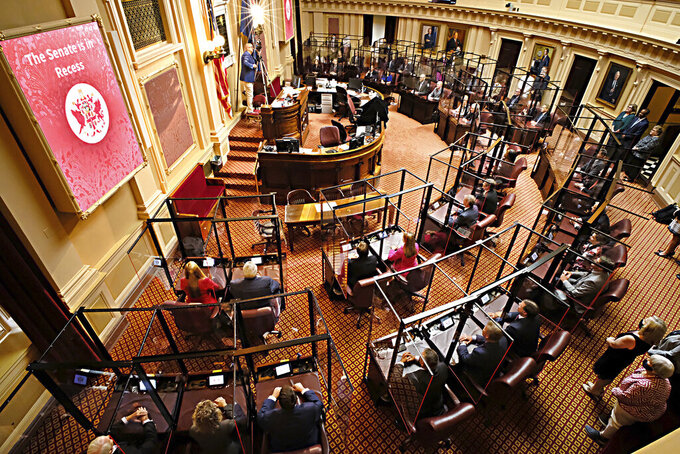 """Photographer Clayton Spangler, top left, from Charleston, W.Va.,, takes a panoramic photo of members and staff of the Virginia Senate before the floor session of the Senate inside the Virginia State Capitol in Richmond, Va., Wednesday, Aug. 4, 2021, on the third day of the General Assembly Special Session.  In past years, a 100-year-old 8x10 film camera was used, but now a small digital camera does the same job. He stated that taking the photo of members inside their fiberglass """"cages"""" was challenging, but the photo came out fine. (Bob Brown/Richmond Times-Dispatch via AP)"""