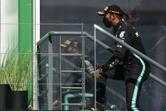 Mercedes driver Lewis Hamilton of Britain climbs to the podium after winning the Portugal Formula One Grand Prix at the Algarve International Circuit near Portimao, Portugal, Sunday, May 2, 2021. (AP Photo/Manu Fernandez)