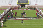 Florida State head football coach Mike Norvell, with daughter Mila and wife Maria, walks between rows of The Marching Chiefs as they play en route to a press conference Sunday, Dec. 8, 2019, in Tallahassee, Fla. Norvell is Florida State's new coach, taking over a Seminoles program that has struggled while he was helping to build Memphis into a Group of Five power. (AP Photo/Phil Sears)