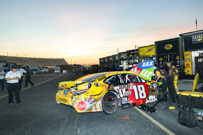 A car is looked over by crew after Kyle Busch pulled out of the pit and parked next to his team's hauler during a NASCAR Cup Series auto race Sunday, Sept. 5, 2021, in Darlington, S.C. (AP Photo/John Amis)