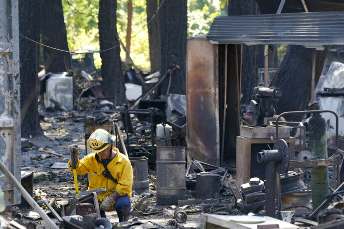 A firefighter working to put out hotspots pauses in the rubble of a structure destroyed by fire, Tuesday, Sept. 8, 2020, after an overnight wildfire in Graham, Wash., overnight south of Seattle. (AP Photo/Ted S. Warren)