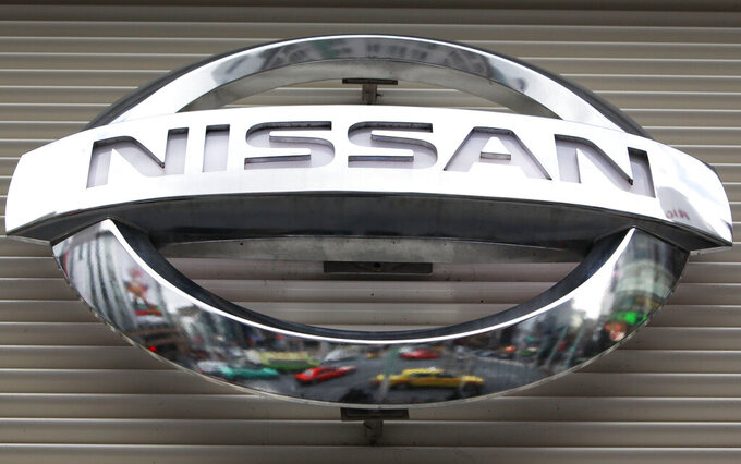 FILE - In this Feb. 8, 2012, file photo, vehicles are reflected on the logo of the Nissan Motors Co. at a showroom in Tokyo's Ginza shopping district. Nissan says its huge factory in Smyrna, Tennessee, will close for two weeks starting Monday, Aug. 16, 2021 due to computer chip shortages brought on by a coronavirus outbreak in Malaysia. (AP Photo/Shizuo Kambayashi, File)