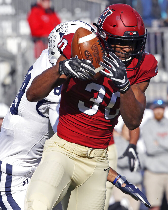 Harvard safety Zach Miller (30) intercepts a pass intended for Yale tight end D. Major Roman, rear, during the first half an NCAA college football game at Fenway Park in Boston, Saturday, Nov. 17, 2018. (AP Photo/Charles Krupa)