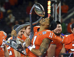 Clemson safety Isaiah Simmons (11) kisses the trophy as he and his teammates celebrate their 30-3 win against Notre Dame in the NCAA Cotton Bowl semi-final playoff football game, Saturday, Dec. 29, 2018, in Arlington, Texas. Clemson won 30-3. (AP Photo/Jeffrey McWhorter)