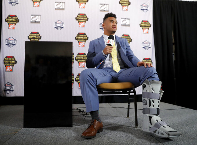 Alabama quarterback Tua Tagovailoa wears a protective boot on his injured foot as he speaks to reporters after winning the Maxwell Award and the Walter Camp honor, Thursday, Dec. 6, 2018, in Atlanta. Tagovailoa was injured in the Southeast Conference championship game against Georgia. (AP Photo/John Bazemore)
