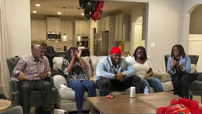 In this still image from video provided by the NFL, Andrew Thomas, center, smiles during the NFL football draft Thursday, April 23, 2020. The New York Giants selected Thomas with the fourth pick. (NFL via AP)