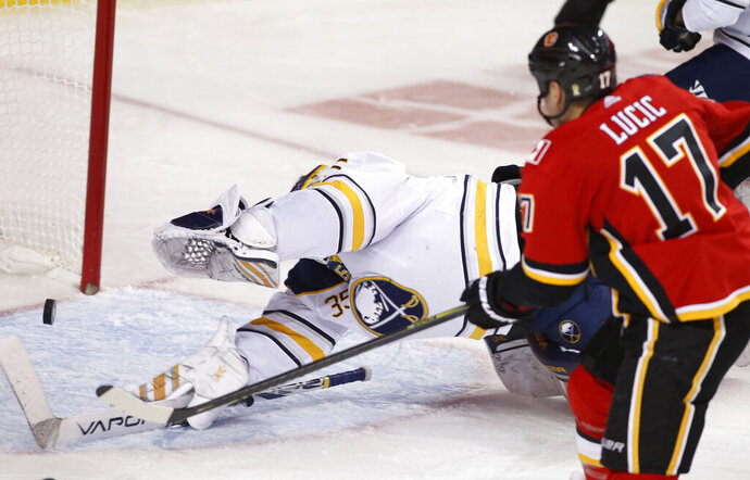 Calgary Flames' Milan Lucic, right, scores his first goal of the season, against Buffalo Sabres goalie Linus Ullmark during the third period of an NHL hockey game Thursday, Dec. 5, 2019, in Calgary, Alberta. (Larry MacDougal/The Canadian Press via AP)