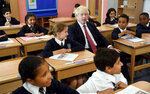 Britain's Prime Minister Boris Johnson, center, visits Pimlico Primary school in London, Tuesday July 10, 2018, to meet staff and students. (Toby Melville/Pool via AP)