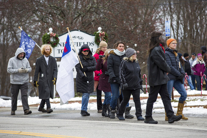 A group of protesters march from the Newfields Town Hall to the Gov. Chris Sununu's house to oppose Sununu's mask mandate and other coronavirus restrictions supported by state and federal public health officials, on Sunday, Jan. 3, 2021 in Newfields, N.H. (Matt Parker/Portsmouth Herald via AP)