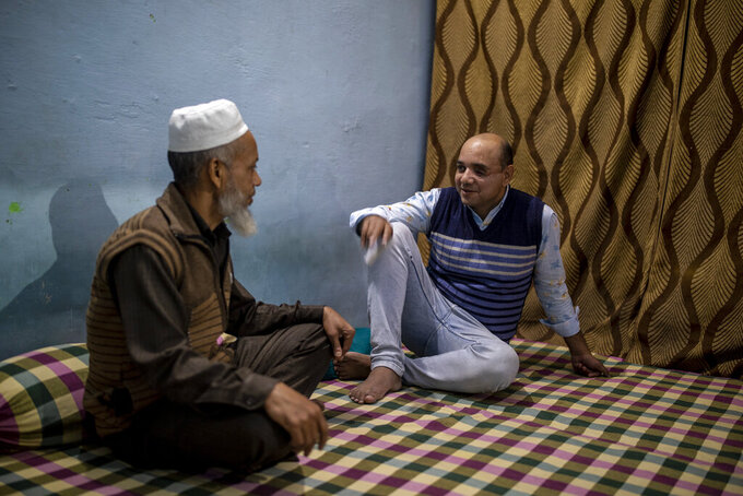 Muhammad Nasir Khan, right,who was shot by a Hindu mob during the February 2020 communal riots, speaks to his father Abdul Jaleel inside his home  in North Ghonda, one of the worst riot affected neighborhood, in New Delhi, India, Friday, Feb. 19, 2021. As the first anniversary of bloody communal riots that convulsed the Indian capital approaches, Muslim victims are still shaken and struggling to make sense of their struggle to seek justice. (AP Photo/Altaf Qadri)