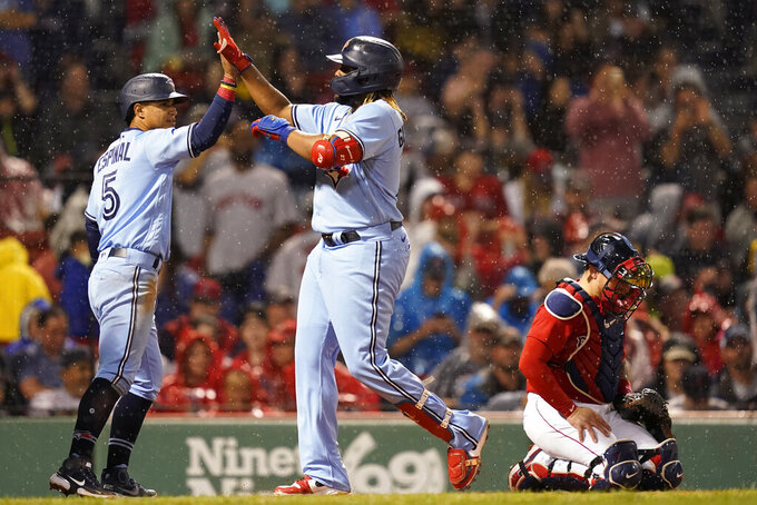 Toronto Blue Jays' Vladimir Guerrero Jr., center, celebrates his three-run home run with Santiago Espinal (5) as Boston Red Sox catcher Christian Vazquez looks at the ground during the fifth inning of a baseball game at Fenway Park, Thursday, July 29, 2021, in Boston. (AP Photo/Elise Amendola)