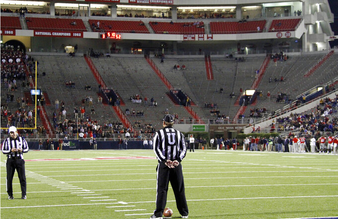 FIUE - In this Nov. 19, 2011, file photo, empty seats are seen in the student section of Vaught-Hemingway Stadium as umpire Rick Lowe waits for LSU and Mississippi players to return to the field during a time out in the fourth quarter of their NCAA college football game in Oxford, Miss. As lock-downs are lifted, restrictions on social gatherings eased and life begins to resemble some sense, sports are finally starting to emerge from the coronavirus pandemic. Many college and pro sports teams already were dealing with declining ticket sales. (AP Photo/Rogelio V. Solis, File)