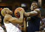 Pittsburgh guard Xavier Johnson, right, fights for a rebound with Virginia forward Mamadi Diakite, left, during the first half of an NCAA college basketball game in Charlottesville, Va., Saturday, March 2, 2019. (AP Photo/Steve Helber)